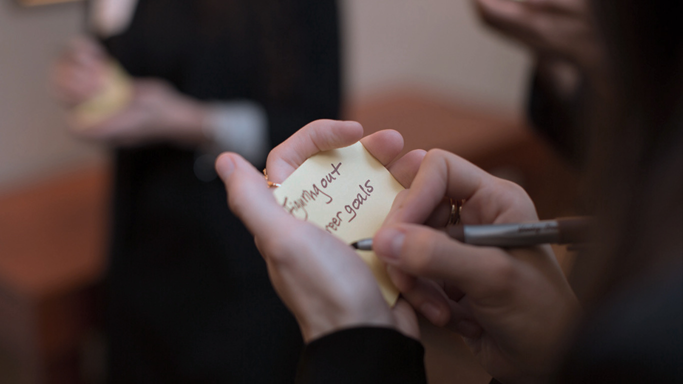 Image: Person writing on sticky note